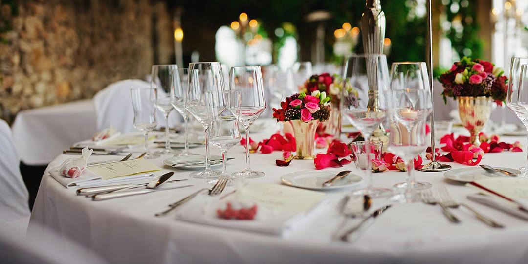 romantyczny stół weselny ozdobiony różami z pełną zastawą