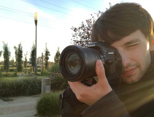 Fotograf z aparatem Nikon w parku