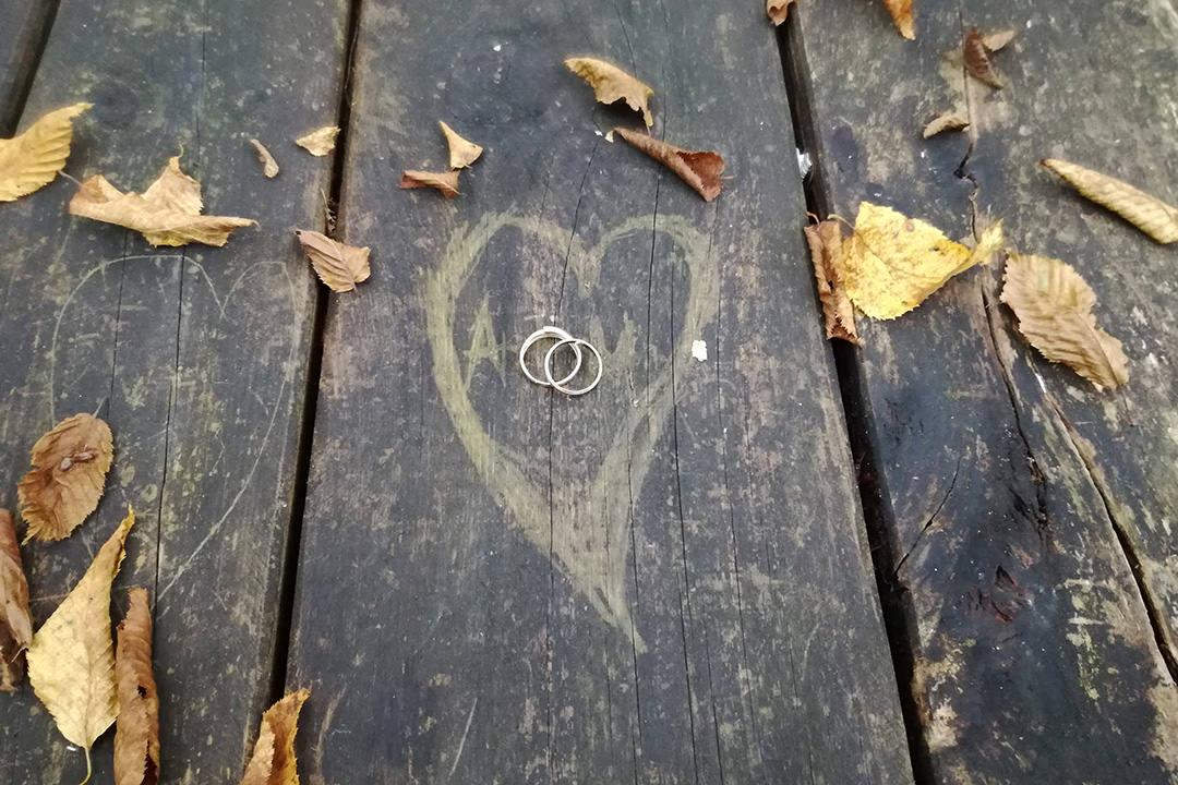 Drewniana ławka, a niej liście i obrączki