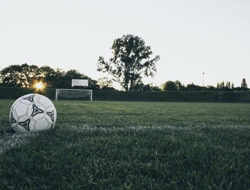 piłka na boisku piłkarskim przy zachodzącym słońcu